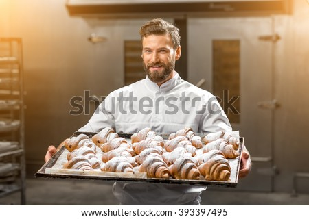 Handsome baker in uniform holding tray full of freshly baked croisants at the manufacturing - stock photo