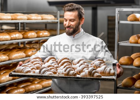 Handsome baker in uniform holding tray full of freshly baked croissants at the manufacturing - stock photo