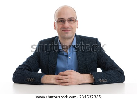handsome bald man sitting at the desk isolated over white