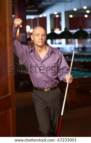 Handsome bald man with pool stick at billiards nightclub - stock photo