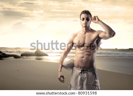 Handsome bare-chested man at the seaside - stock photo