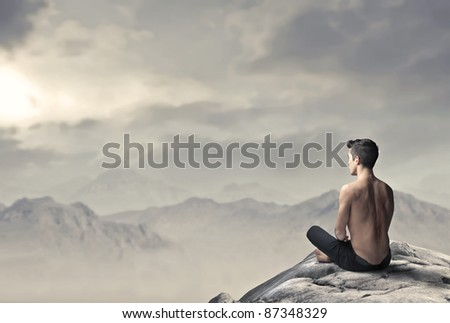 Handsome bare-chested man sitting on a peak over the mountains - stock photo