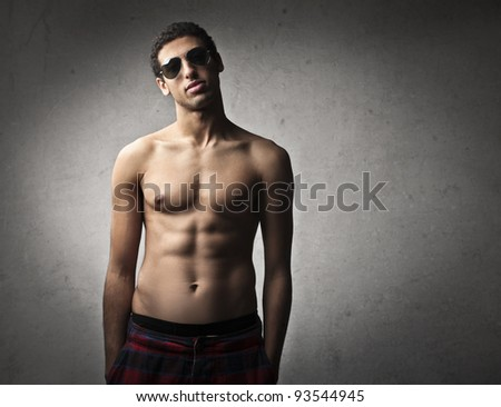 Handsome bare-chested man wearing sunglasses - stock photo