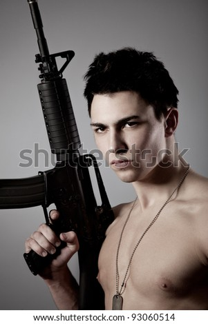 Handsome bare-chested soldier is holding a rifle on black background