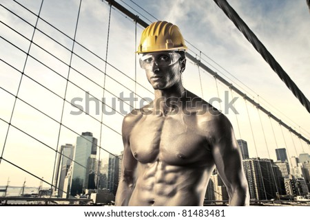 Handsome bare-chested worker with cityscape in the background - stock photo