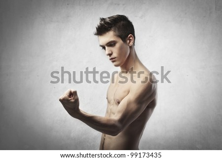 Handsome bare-chested young man showing his biceps