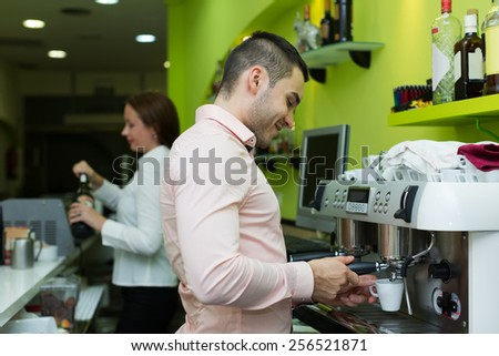 Handsome barista making coffee and bartenter at background  - stock photo