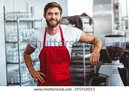 Handsome barista smiling at the camera at the cafe - stock photo