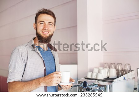 handsome barista with beard making coffee in a cafe