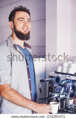 handsome barista with beard making coffee in a cafe - stock photo