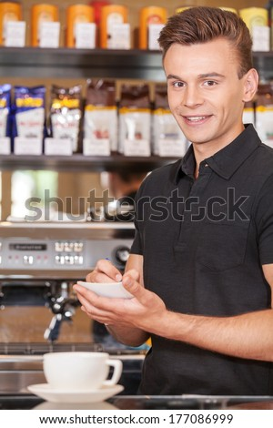 handsome barista writing check and smiling. attractive male making coffee and watching