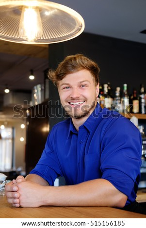 Handsome barman having fun at bar counter in bakery.