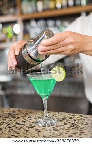 Handsome barman pouring a cocktail in a glass in a pub - stock photo