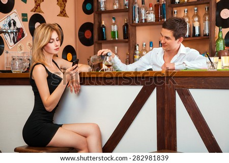 handsome barman pours a glass of alcohol at the girl as she talks on a cell phone. horizontal photo - stock photo