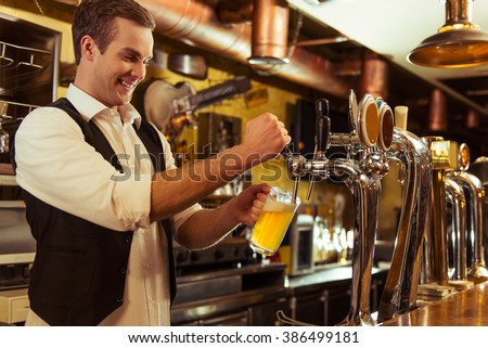 Handsome bartender is smiling and filling a glass with beer while standing at bar counter in pub - stock photo
