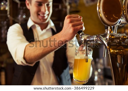 Handsome bartender is smiling and filling a glass with beer while standing at bar counter in pub, close-up - stock photo