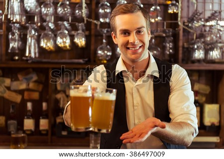 Handsome bartender is smiling, looking at camera and holding glasses of beer while standing at bar counter in pub - stock photo