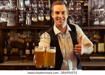 Handsome bartender is smiling, showing OK sign and holding glasses of beer while standing at bar counter in pub