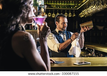 Handsome bartender serving cocktail to beautiful woman in a pub - stock photo