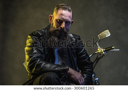 Handsome Bearded Biker Man in Leather Jacket Sitting on his Motorcycle and Looking Into the Distance Against Gray Wall Background - stock photo
