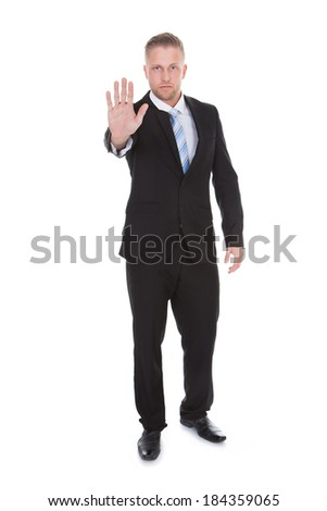Handsome bearded businessman holding up his hand in a stop or halt gesture as he forbids entry or brings something to an end  isolated on white - stock photo
