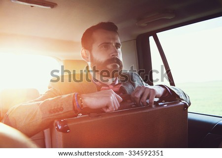 handsome bearded businessman sitting on back seat of car with  suitcase - stock photo