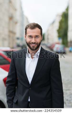 Handsome bearded businessman with a friendly smile standing outdoors in an urban environment - stock photo