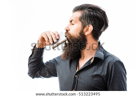 handsome bearded fashion man with stylish hair mustache and long beard on serious face drinking from metallic flask isolated on white