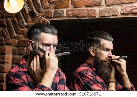 Handsome bearded man hipster with stylish haircut and beard holding old fashion razor in red checkered shirt near mirror with serious face in beauty salon or barbershop as barber near brick wall