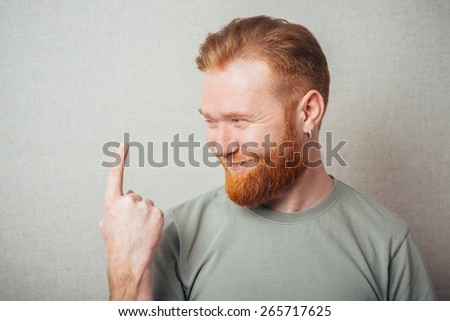 Handsome bearded  man in blue collar shirt smiles and points with finger  - stock photo