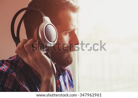 handsome bearded man  in headphones listening to music