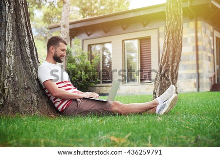 Handsome bearded man is sitting in the backyard under the tree with his laptop - stock photo