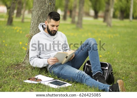 Handsome bearded man learning in park concept