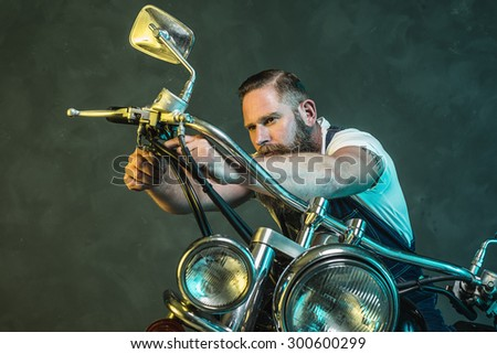 Handsome Bearded Man Repairing his Vintage Motorcycle Seriously Against Black Smoky Wall Background. - stock photo