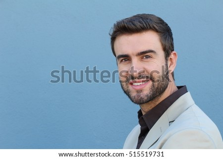 Handsome bearded man smiling isolated on blue with copy space