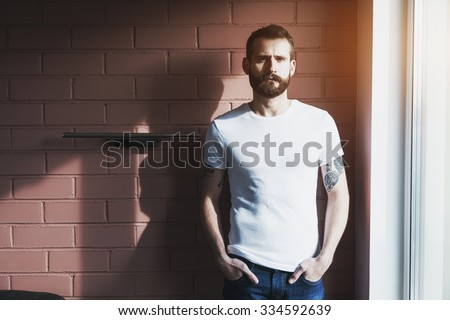 handsome bearded man wearing blank white t-shirt on brick wall background - stock photo