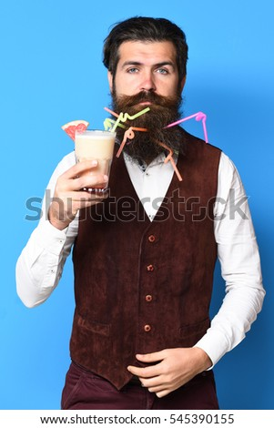 handsome bearded man with colorful tubes in long beard and mustache has stylish hair on serious face holding glass of alcoholic cocktail in vintage suede leather waistcoat on blue studio background