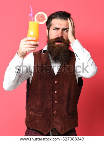 handsome bearded man with long beard and mustache has stylish hair on disappoint face holding glass of alcoholic cocktail in vintage suede leather waistcoat on red studio background