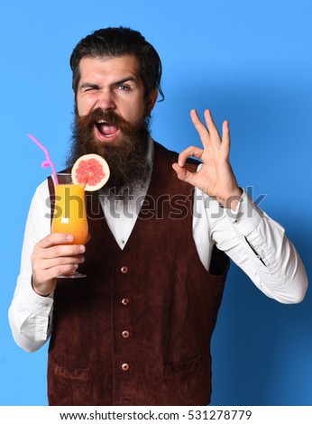 handsome bearded man with long beard and mustache has stylish hair on satisfied face holding glass of alcoholic cocktail in vintage suede leather waistcoat on blue studio background