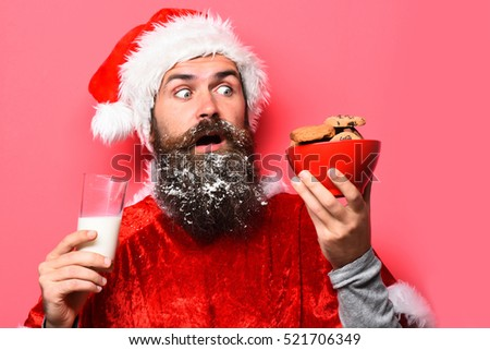 handsome bearded man with stylish mustache and long snowy beard on funny face holding glass of milk with chocolate chip cookies in red santa suit on studio background