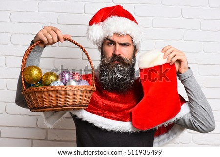 handsome bearded man with stylish mustache and long snowy beard on serious face holding christmas basket with colorful balls and christmas sock in red santa suit on white brick wall background