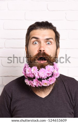 handsome bearded man with stylish mustache and shirt with pink autumn flowers in long beard on surprised face on white brick wall background