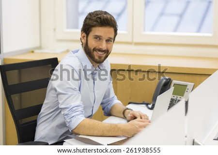 Handsome bearded man working in office on computer. looking camera - stock photo
