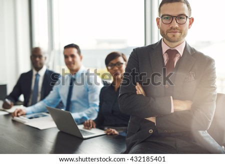 Handsome bearded professional sitting on desk corner beside three coworkers in front of large office window - stock photo