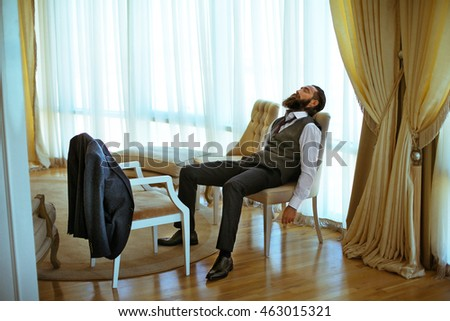 Handsome bearded strong man relaxing in leather chair