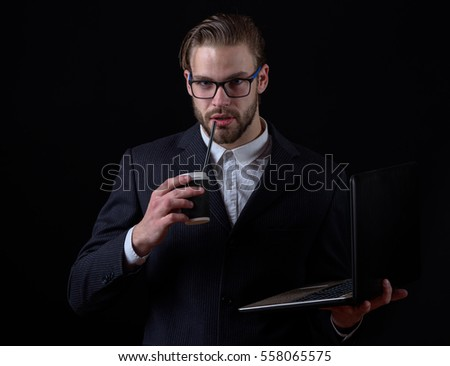 handsome bearded stylish business man in elegant black suit in glasses holding laptop with thoughtful face and coffee cup in studio on black background, copy space