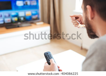 Handsome bearded young man with remote control watching tv and eating at home - stock photo