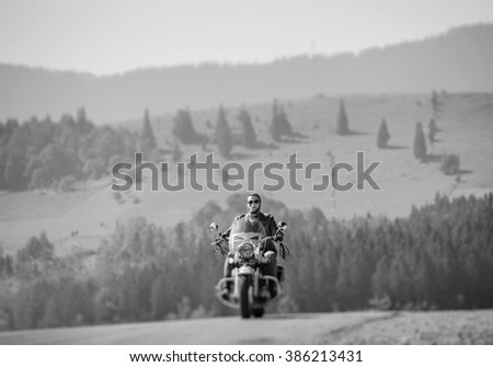 Handsome biker in sunglasses on mountainous road, man is riding his custom made travel motorbike. Sunny day in the mountains. Tilt shift soft effect. Black and white - stock photo