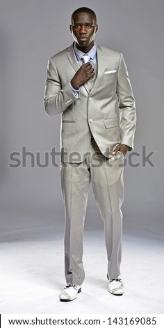 Handsome black man adjusting tie as he walks towards the camera. - stock photo