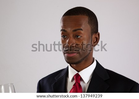 Handsome black man in a business suit, drinking a glass of white wine